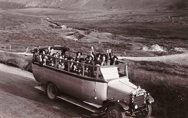 Black and white photo of an early, open top bus with people waving out the top
