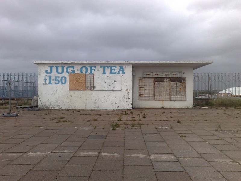 A closed and dilapidated sea-front cafe with 'Jug of Tea' written on it
