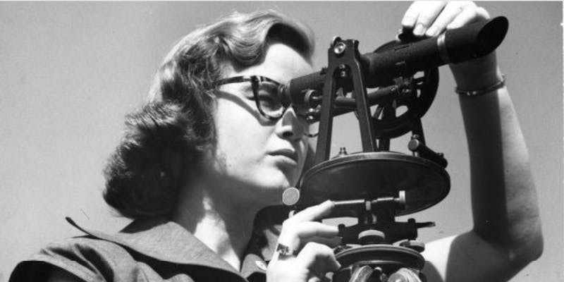 Black and white photo of woman looking through a telescope