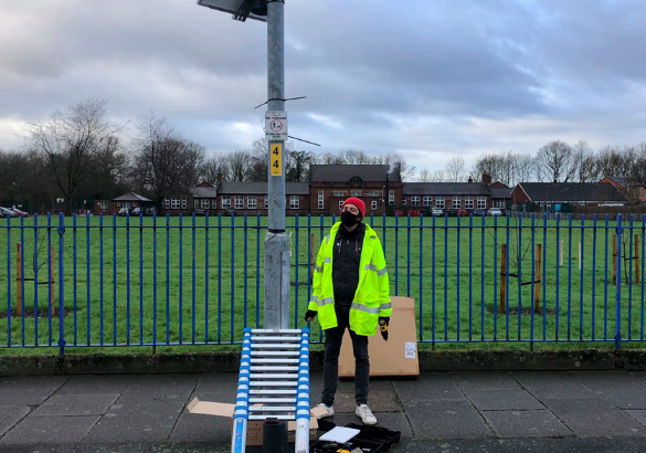 A white person standing in high-vis next to a lamppost, after installing EarthSense air-quality sensors